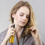 Девушка с флаконом масла изучает кончики волос