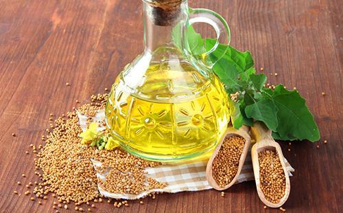 Стеклянный кувшинчик с горчичным маслом и рассыпанные семена