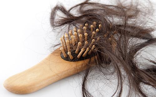 Пучок волос в зубцах деревянной щётки